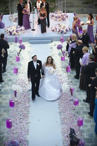 bride-and-groom-walk-up-white-aisle-with-purple-flowers
