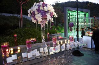 glass-table-with-large-flower-arrangement-and-floating-candles