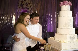 bride-and-groom-cut-white-cake-with-rhinestones