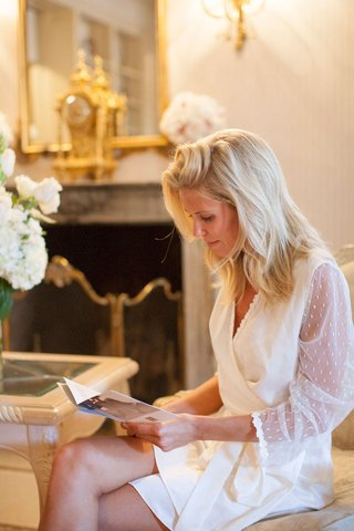 bride-in-white-robe-and-natural-hair-reading-a-card-from-groom-before-getting-hair-and-makeup-done