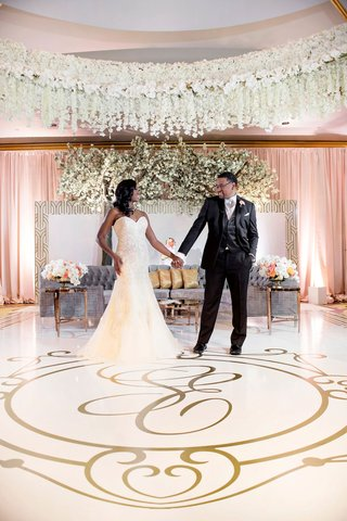 bride-groom-hold-hands-in-reception-ballroom-gold-monogram-dance-floor-grey-tufted-sofa-lounge