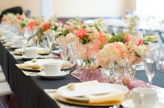 bridal-shower-table-with-floral-runner-of-pink-white-and-orange-flowers-in-round-vases-with-glitter