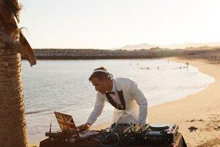 destination-wedding-dj-performing-on-the-beach-in-a-white-tuxedo