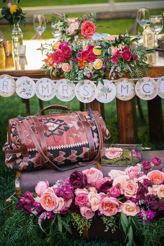 outdoor-wedding-reception-with-a-closed-antique-suitcase-filled-with-a-variety-of-pink-peach-roses