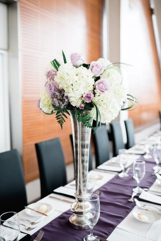 long-rectangle-wedding-table-with-purple-runner-silver-vase-white-hydrangea-purple-rose-and-greenery