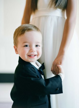 flower-girl-holding-hand-of-ring-bearer-who-smiles-at-camera-in-bow-tie-and-suit