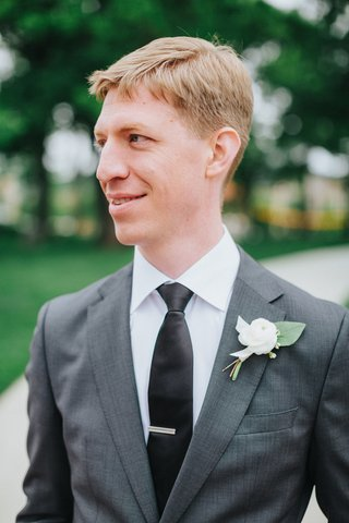groom-in-grey-suit-black-tie-with-silver-tie-bar-white-flower-and-green-leaf-boutonniere