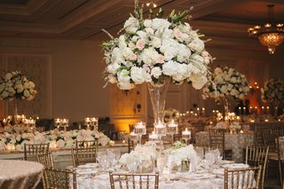 indoor-reception-with-gold-chairs-and-cream-flower-arrangements