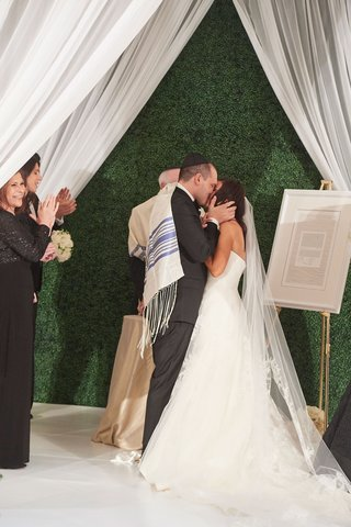 washington-dc-wedding-ceremony-tall-green-hedge-wall-white-drapery-chuppah-white-tile-kiss-jewish