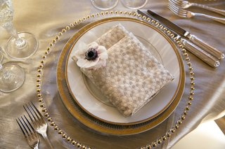 textured-patterned-napkin-at-wedding-reception-with-anemone-blossom-in-the-corner