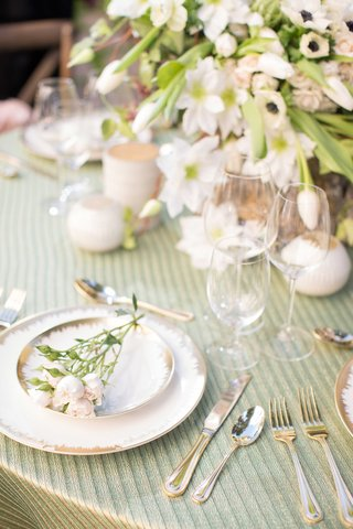 white-and-gold-charger-plates-with-pink-flowers-on-green-table-linen-lush-floral-arrangement