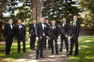 groom-and-groomsmen-in-black-tuxedos-and-white-rose-boutonnires