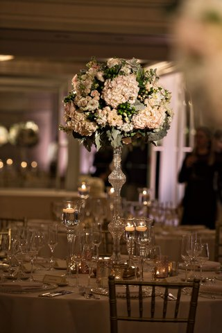 tall-flower-arrangement-at-wedding-reception-round-table-floating-candles-crystal-riser-hydrangea