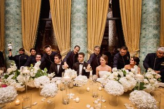 bride-groom-groomsmen-and-bridesmaids-as-the-bridal-party-are-served-drinks-on-gold-table-linen