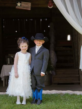 flower-girl-in-tank-ruffle-dress-with-ring-bearer-in-grey-suit-with-cowboy-boots-and-hat