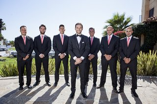 groom-in-tuxedo-with-bow-tie-and-groomsmen-in-suits-and-coral-pink-ties-at-destination-wedding