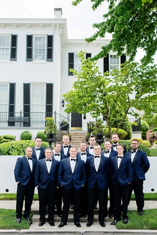 groom-with-groomsmen-in-front-of-wedding-venue-with-navy-tuxedo-jacket-black-bow-tie-pants