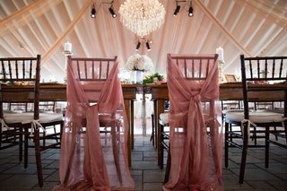 sheer-pink-fabric-tied-around-the-reception-chairs-for-both-the-bride-and-the-groom