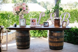 guest-book-table-with-barrel-base-rustic-wooden-initials-painted-white-framed-photos