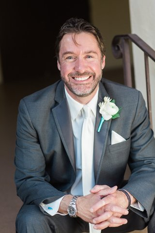 idw-publishing-founder-ted-adams-in-a-grey-suit-white-tie-boutonniere-on-his-wedding-day