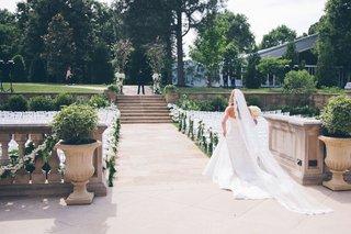bride-walking-through-chairs-to-meet-groom
