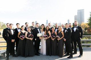 bride-and-groom-on-balcony-in-chicago-with-bridesmaids-in-charcoal-dresses-and-groomsmen-in-tuxedos