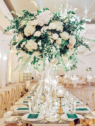 wedding-reception-long-table-modern-gold-chairs-white-greenery-centerpiece-green-menu-gold-candles
