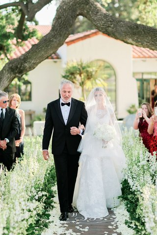bride-in-carolina-herrera-ball-gown-in-blusher-veil-walking-with-her-father-down-the-aisle