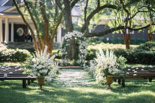 outdoor-plantation-like-wedding-white-flowers-greenery-benches