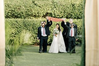 bride-in-wedding-dress-by-the-boutique-by-b-belle-events-walking-down-aisle-with-cousins-brothers