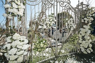white-wrought-iron-gate-adorned-with-flowers