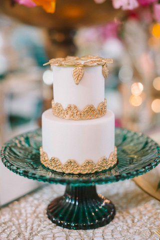 two-tier-small-white-wedding-cake-gold-accents-blue-stand