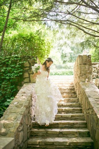 bride-walks-on-stone-steps-with-flower-motif-dress