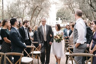 wedding-ceremony-outdoor-vibiana-redbird-father-in-grey-suit-bride-tea-length-dress-wood-chairs