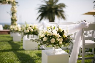 small-floral-arrangements-lining-aisle-white-green-roses-on-white-stands-outdoors-grass-wedding