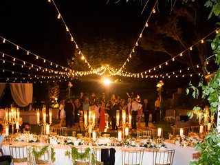 outdoor-reception-area-long-table-white-linens-candelabra-strings-lights-guests-dancing-night