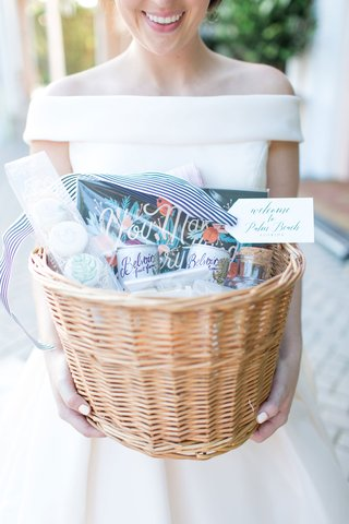bride-in-off-shoulder-wedding-dress-white-manicure-holding-welcome-basket-with-goodies