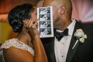 bride-and-groom-kiss-behind-photo-booth-strip