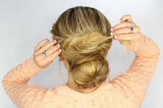bride-wrapping-hair-around-bun-with-fishtail-braid