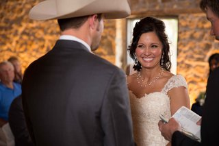 bride-at-altar-with-cowboy-groom-smiling-with-pearl-jewelry