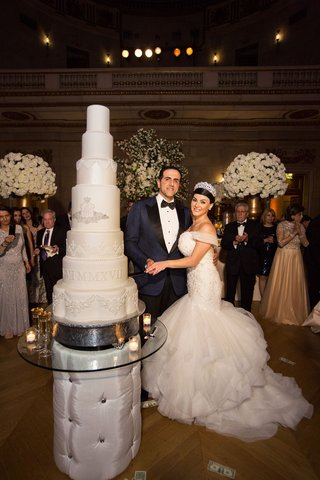bride-and-groom-with-tall-seven-layer-wedding-cake-monogram-and-roman-numerals-wedding-date-opulent