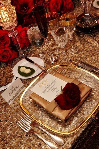 wedding-tablescape-with-gold-sequins-red-roses-on-gold-napkin-clear-gold-rimmed-charger