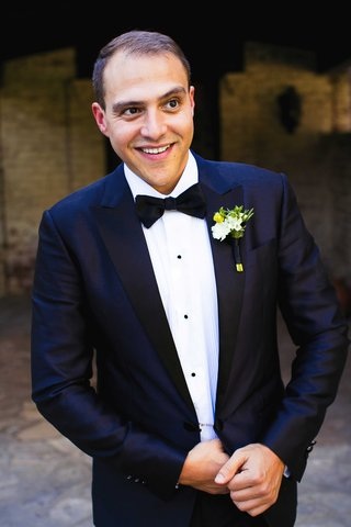 a-groom-smiling-in-a-dark-blue-tuxedo-and-black-bow-tie-with-green-and-white-boutonniere
