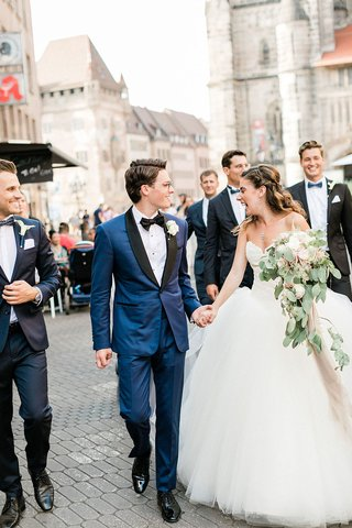 wedding-in-germany-bride-and-groom-walking-with-wedding-party-family-down-streets-of-german-town