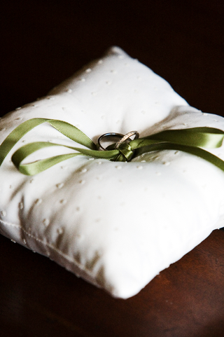 rings-tied-to-white-pillow-with-green-ribbon