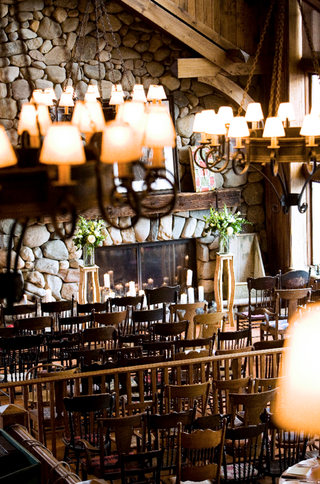 lodge-with-wooden-chairs-stone-fireplace-and-rustic-lampshade-chandeliers