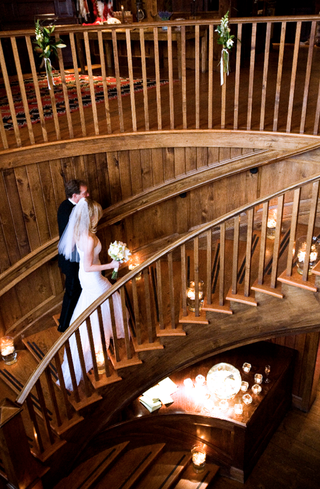 bride-and-groom-walk-up-wooden-staircase-in-lodge