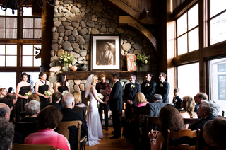 wedding-ceremony-in-rustic-lodge-with-large-windows-and-stone-fireplace