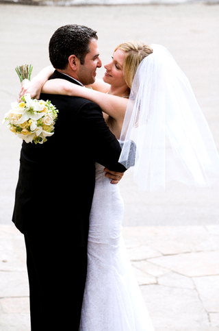 groom-hugs-bride-holding-yellow-and-white-bouquet