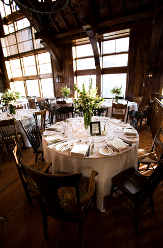 wooden-lodge-with-tall-windows-and-tables-covered-in-white-linens